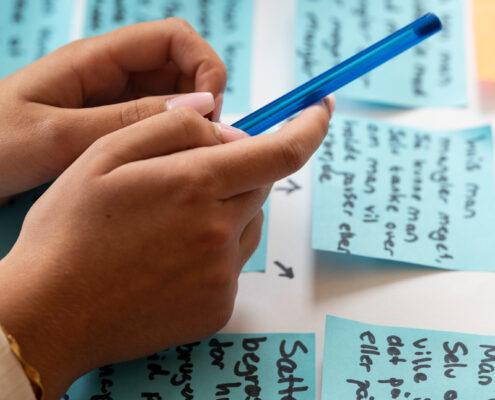 ungt menneske holder en blå kuglepen og har sine hænder over flere blå post it med tekst på